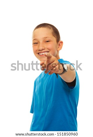 Portrait of happy young boy pointing at camera with his finger, standing isolated on white - stock photo