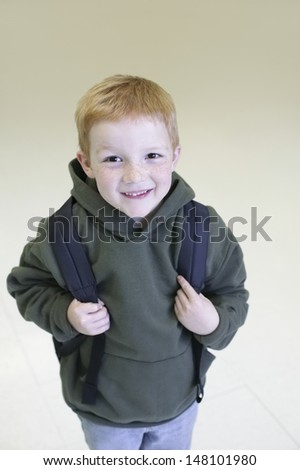 Portrait of happy young boy with backpack standing over colored background