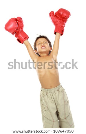 portrait of happy young boy with boxing glove. winning pose - stock photo