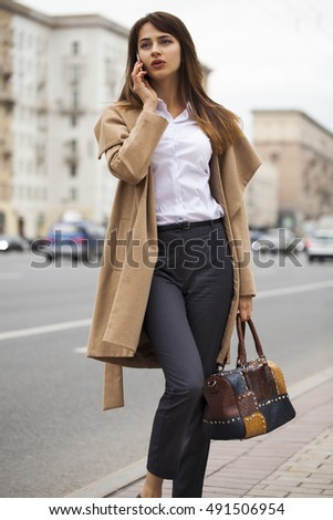 Portrait of happy young brunette woman in beige coat talking on the phone outdoors autumn street