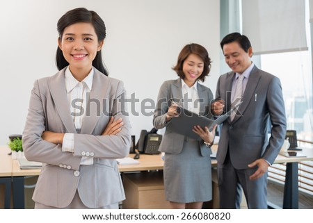 Portrait of happy young business lady and her coworkers discussing document in the background