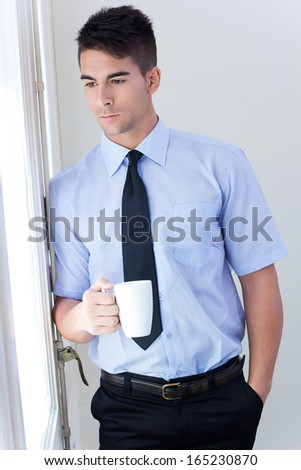 Portrait of happy young business man relaxing with coffee cup  in modern office