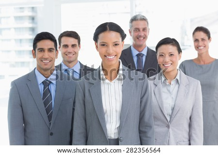 Portrait of happy young business people standing in office