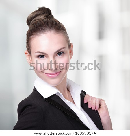 Portrait of happy young business woman at office, caucasian - stock photo