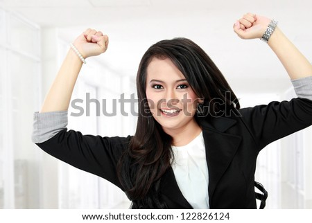 Portrait of happy young business woman celebrating success