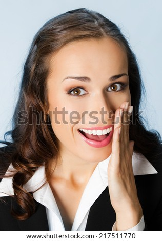 Portrait of happy young business woman covering with hand her mouth, over blue background - stock photo
