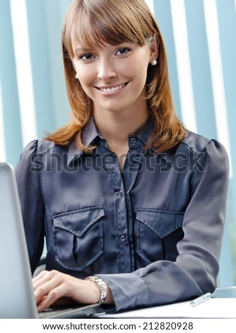 Portrait of happy young business woman working with laptop at office - stock photo