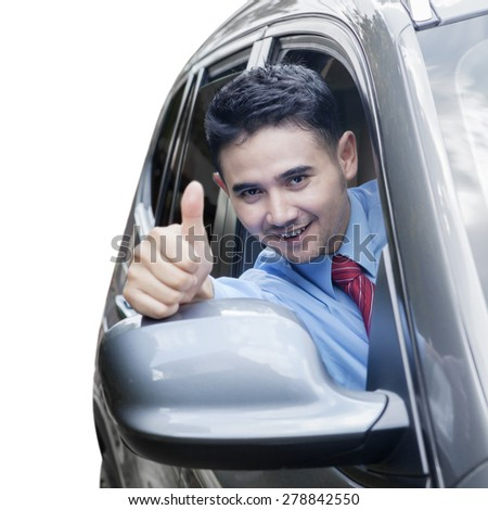 Portrait of happy young businessman drive a new car while showing thumb up - stock photo