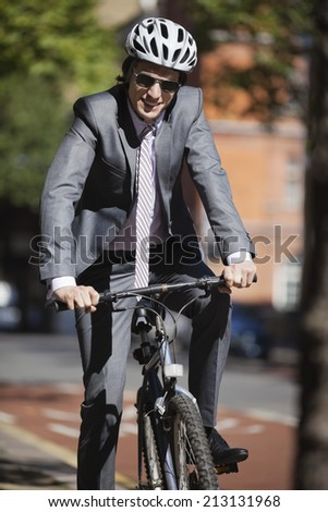 Portrait of happy young businessman riding bicycle - stock photo