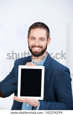 Portrait of happy young businessman showing digital tablet in office - stock photo