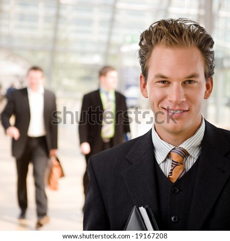 Portrait of happy young businessman smiling at office. - stock photo