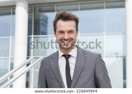 Portrait of happy young businessman standing outside office building - stock photo