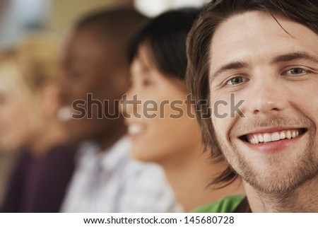 Portrait of happy young businessman with colleagues in background - stock photo