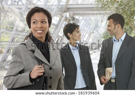 Portrait of happy young businesspeople at office building, talking, smiling. - stock photo