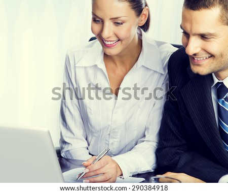 Portrait of happy young businesspeople working with laptop at office workplace - stock photo