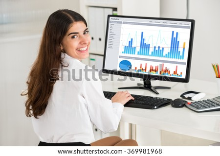 Portrait of happy young businesswoman analyzing financial graphs on computer at desk in office - stock photo