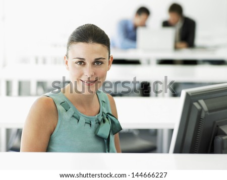 Portrait of happy young businesswoman at computer desk with male colleagues in background