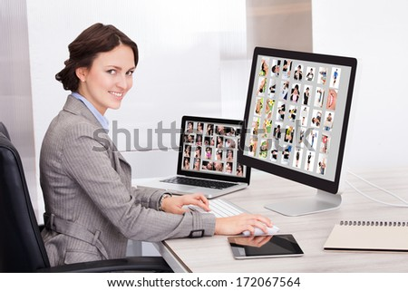 Portrait Of Happy Young Businesswoman Browsing Pictures On Computer - stock photo