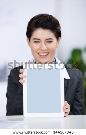 Portrait of happy young businesswoman displaying digital tablet at counter - stock photo