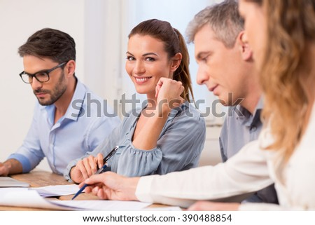 Portrait of happy young businesswoman looking at camera during a meeting. Beautiful businesswoman in a meeting. Business people in a row discussing and working together during a meeting in office. - stock photo
