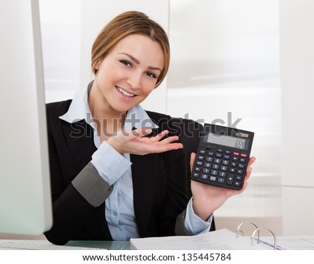 Portrait Of Happy Young Businesswoman Showing Calculator - stock photo