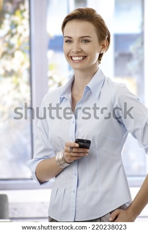 Portrait of happy young businesswoman standing in office, holding mobilephone, looking away.