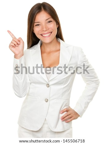 Portrait of happy young businesswoman with hand on hip pointing sideways over white background - stock photo