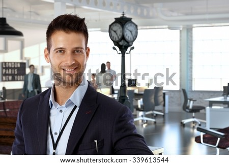 Portrait of happy young caucasian business office worker, wearing suit, looking at camera, smiling. - stock photo