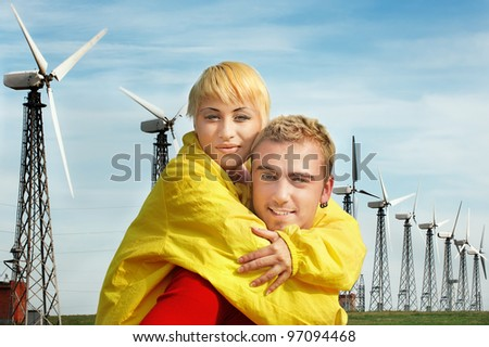 Portrait of happy young couple against windmills.