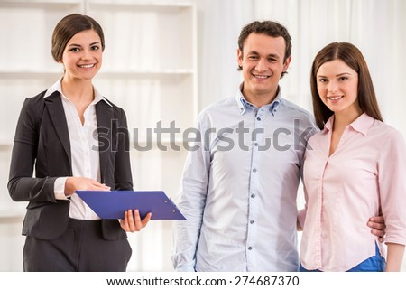 Portrait of happy young couple and female realtor in a new flat. - stock photo