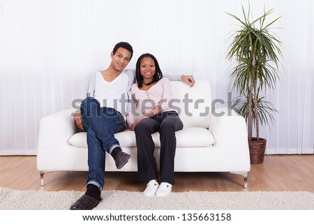 Portrait Of Happy Young Couple At Home Smiling