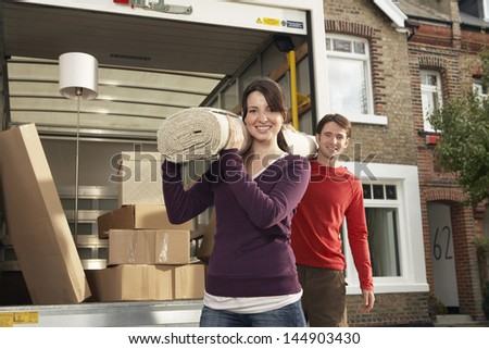 Portrait of happy young couple carrying rolled carpet by moving van - stock photo