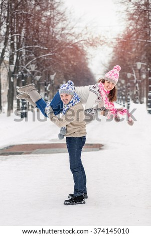 Portrait of happy young couple having fun in winter park.
