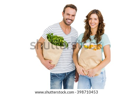 Portrait of happy young couple holding bag of vegetables on white background