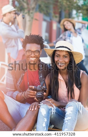 Portrait of happy young couple holding camera - stock photo