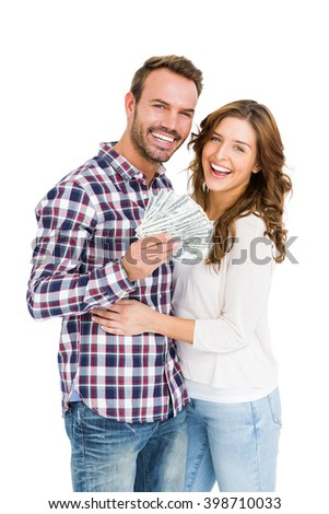 Portrait of happy young couple holding fanned out currency note on white background