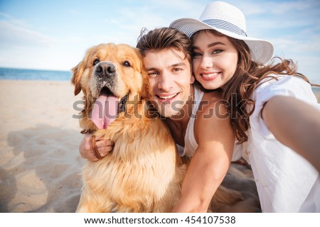 Portrait of happy young couple hugging their dog and smiling on the beach - stock photo