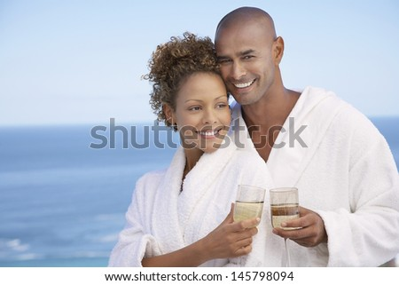 Portrait of happy young couple in bathrobes holding drinks with ocean in background