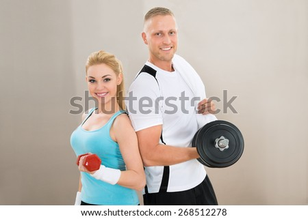 Portrait Of Happy Young Couple Lifting Dumbbells - stock photo