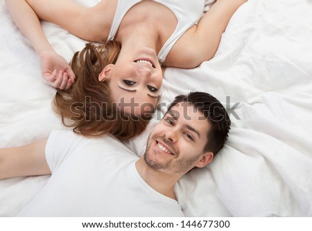 Portrait of happy young couple lying on bed together - stock photo