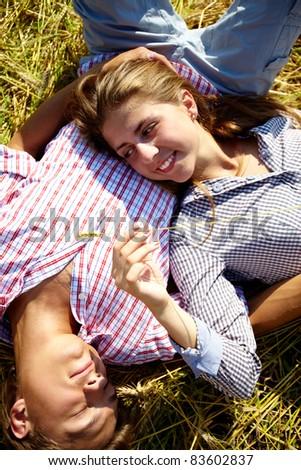 Portrait of happy young couple lying on hay outside - stock photo