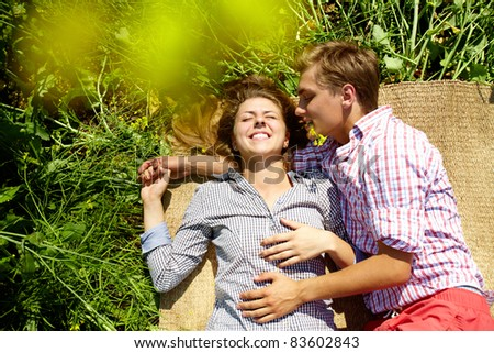 Portrait of happy young couple lying on straw rug outside