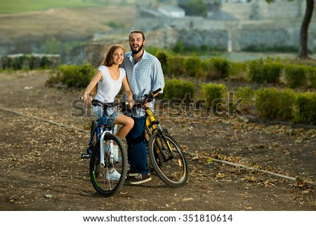 Portrait of happy young couple of bicyclists smiling in the street