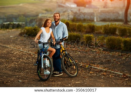 Portrait of happy young couple of bicyclists talking in the street