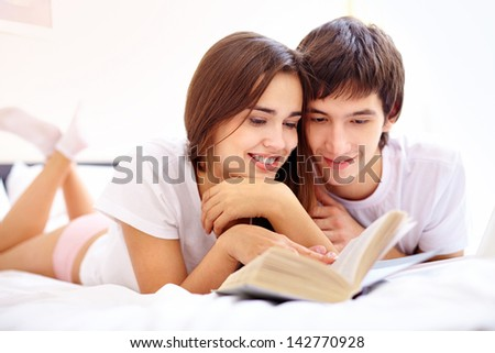 Portrait of happy young couple reading in bed together