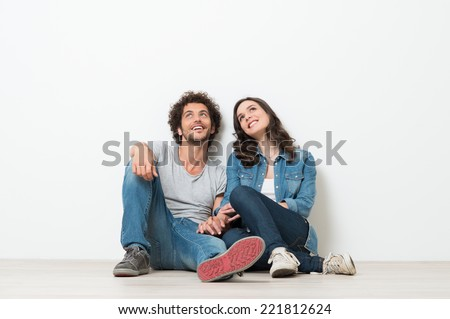 Portrait Of Happy Young Couple Sitting On Floor Looking Up Ready for your text or product - stock photo