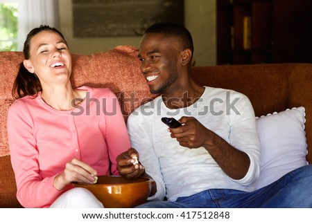 Portrait of happy young couple sitting on sofa watching movie and eating popcorn at home - stock photo
