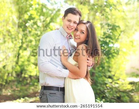 Portrait of happy young couple together in sunny summer day - stock photo