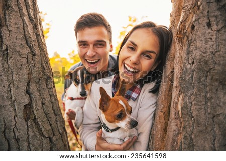 Portrait of happy young couple with dogs outdoors in autumn park looking out from from tree - stock photo