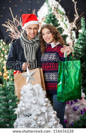 Portrait of happy young couple with shopping bags standing at Christmas store - stock photo